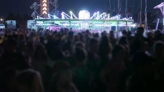 People Having Fun On Bright Carnival Rides At Night