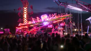 People Having Fun On The Bright Carnival Rides At Night