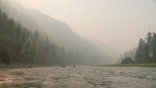 Rafts Floating Down A River Through Forrest Filled With Smoke From Fire