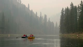 Rafts Floating Down River Through Forrest Filled With Smoke At Sunset