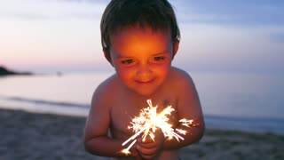 Slow Motion A Boy Playing With Glowing Orange Sparklers On Beach