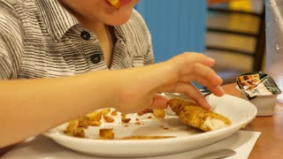 Slow Motion Of Boy Having Chicken Fingers At Restaurant With Family