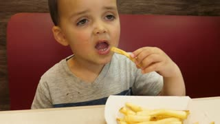 Slow Motion Of Boys Eating Unhealthy French Fries In Fast Food Restaurant
