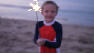 Slow Motion Of Child Playing With Glowing Sparklers On Beach