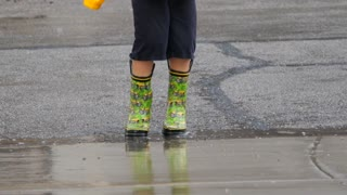 Slow Motion Shot Of A Boy Playing In A Rain Storm Puddles With Boots