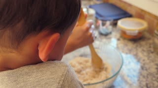 Slow Motion Shot Of Boy Helping His Mother Cook In A Kitchen