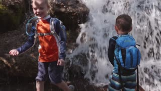 Slow Motion Shot Of Boys Playing In Mountain Waterfall