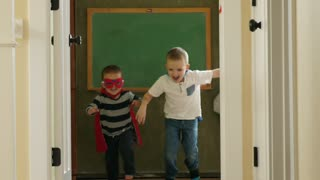 Slow Motion Shot Of Two Young Boys Racing In Super Hero Capes