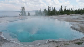 Steam Rising From Natural Hot Pot In Yellowstone National Park With People