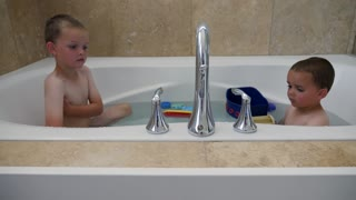 Two Siblings Taking A Warm Bath With Toys In Their House