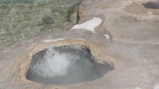 Water Boiling From Natural Hot Pot By Lake In Yellowstone National Park