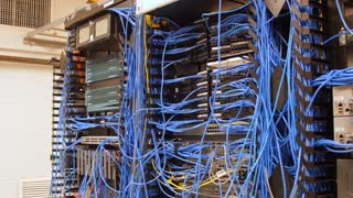 Web of cables in telecommunications room