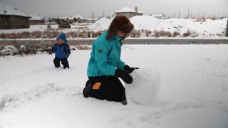 woman and her toddler making a snowman