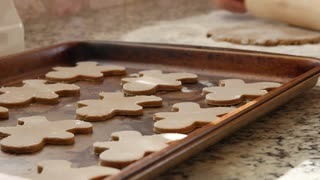 Woman baking gingerbread men for the holidays