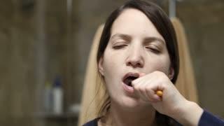 Woman brushing her teeth before bedtime