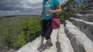 Woman climbs down tall stairs of ruin at Ek Balam Mayan in Mexico