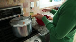 woman cooking popcorn on a gas stove