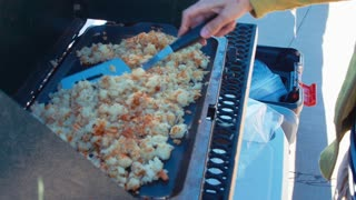 Woman cooking potato hash browns while camping