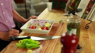 woman cuts a green pepper for a greek salad