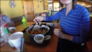 Woman eats a burrito in mexican restaurant