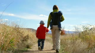 Woman hiking with her boys on the boardwalk by river low shot