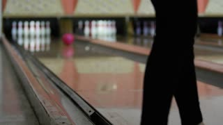 Woman hits pins with bowling ball in bowling alley