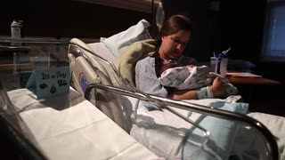 woman holding newborn baby in hospital bed