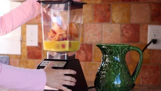Woman making a fruit smoothie