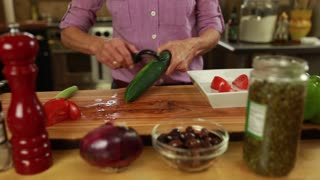 woman peeling a cucumber for a greek salad