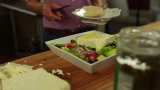 woman preparing a delicious greek salad with feta cheese