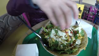 Woman putting dressing on her mexican salad in restaurant