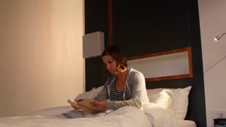 Woman reading a book in a cozy bed at hotel room