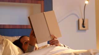Woman reading a book in comfortable bed at hotel room