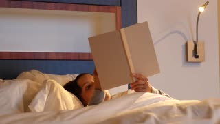 Woman reading book in comfortable bed at hotel room