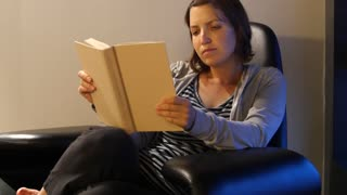 Woman reading book in hotel room modern chair