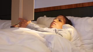 Woman reading her book in a comfortable bed at hotel room