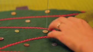woman sewing buttons on christmas advent calendar
