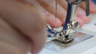 Woman sewing fabric with sewing machine close up
