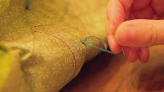 woman ties not with sewing needle