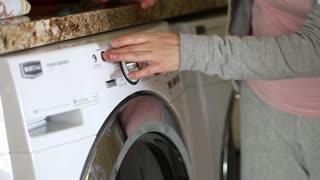 woman turns on washing machine
