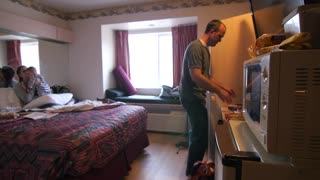 Young family cooks frozen pizza in hotel room microwave