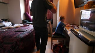 Young family eating pizza in a small hotel room