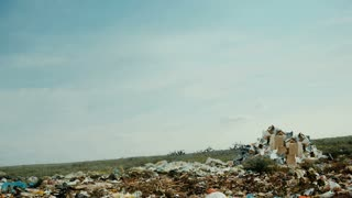An unidentified girl running with hair flying in the wind around the huge trash heap.