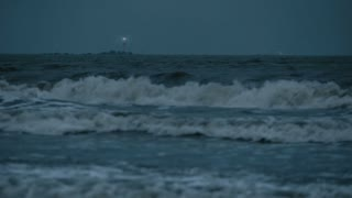 Beacon illuminating the night stormy sea.