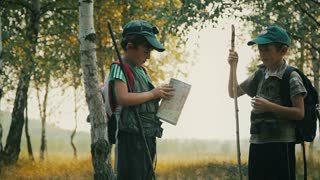 Boys travelers with backpacks studying the route map in a sunny summer day.