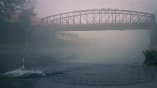 Bridge on river and morning fog.