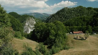Carpathian Mountains landscape with rocks, wooded hills and meadows.