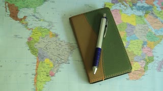 Close-up of a notebook with a pen and world map on the desk.