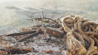 Close up of a representation of the Jesus Christ crown of thorns with nails, hammer, pliers and a rope placed on a stone.