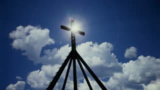 Cross and sun with moving white clouds against blue sky.